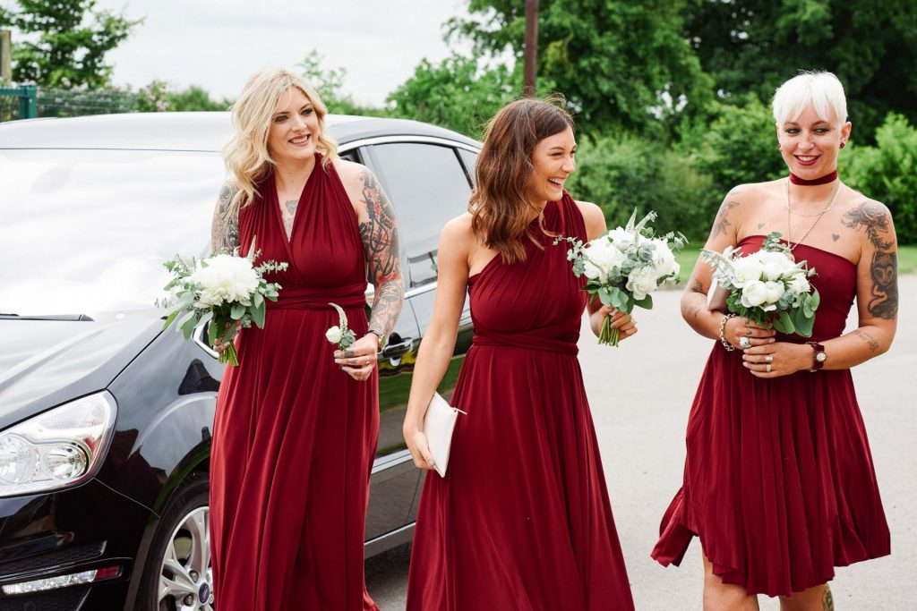 Tattooed bridesmaids wearing red dresses arriving at Pheasantry Brewery wedding venue