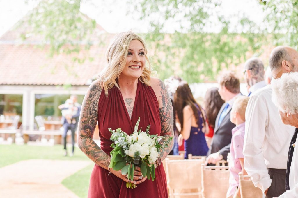 Tattooed bridesmaid wearing a red dress walking down outside wedding aisle
