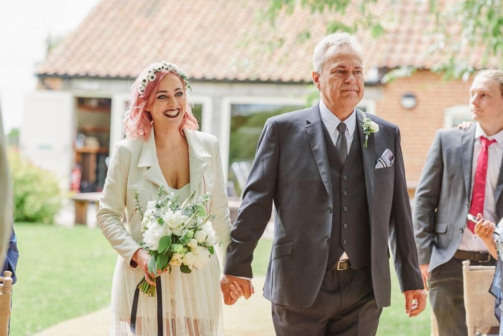 Festival style bride and her father walking down outside wedding aisle at The Pheasantry Brewery.