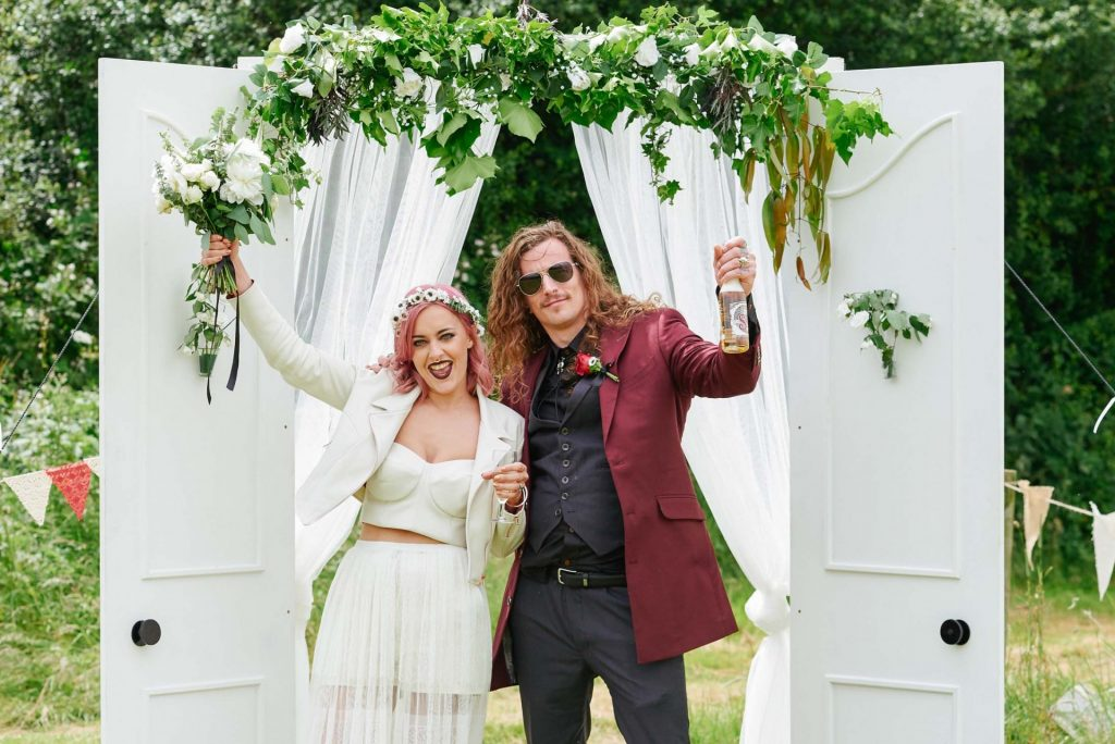 Rock n roll bride and groom stood outside and in front of a white door whilst celebrating