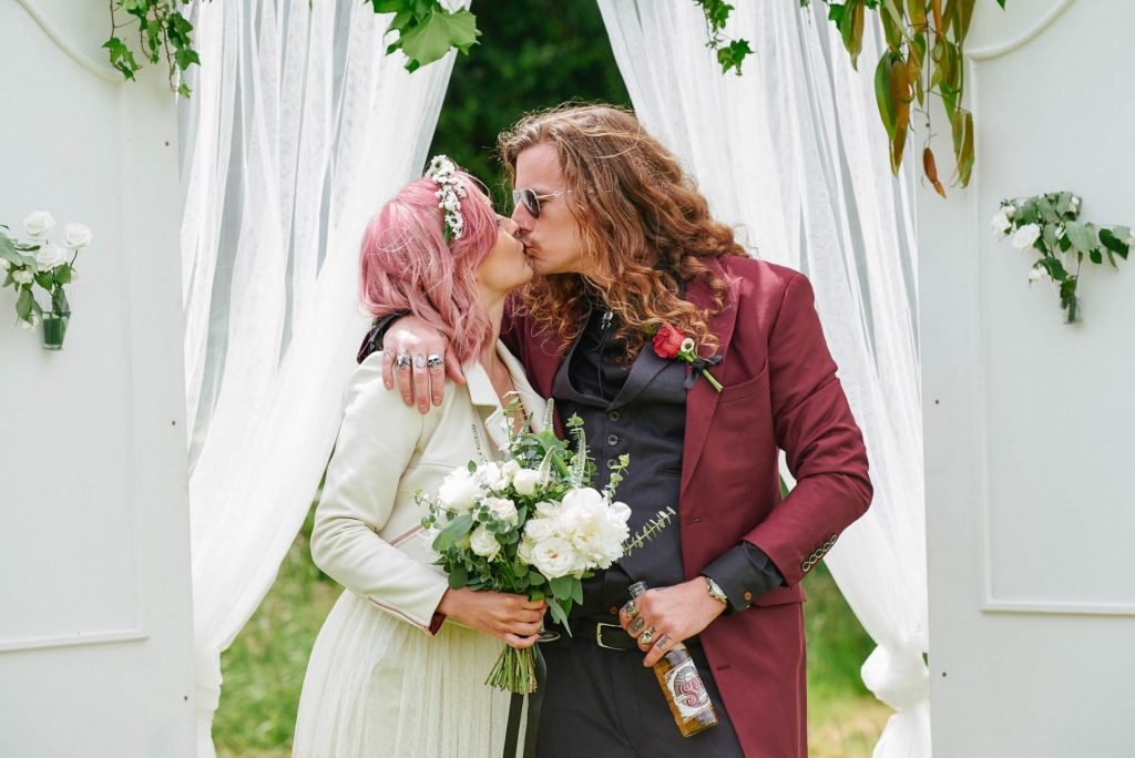 Bride and groom kissing at their rock n roll wedding at The Pheasantry Brewery