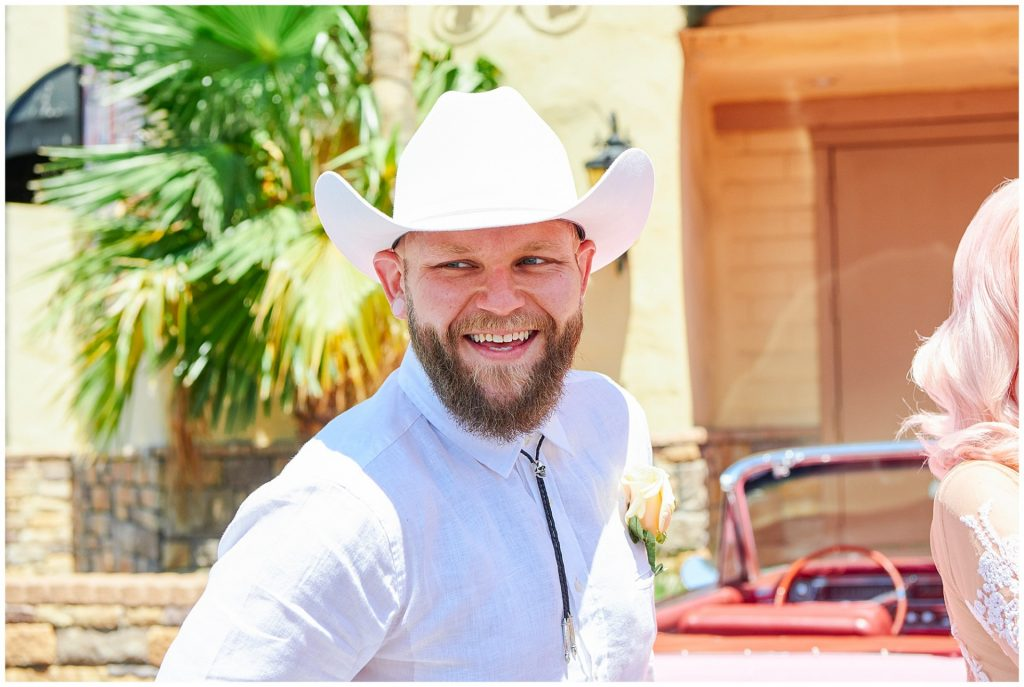Groom wearing white cowboy hat and shirt smiling after his destination Vegas elopement ceremony