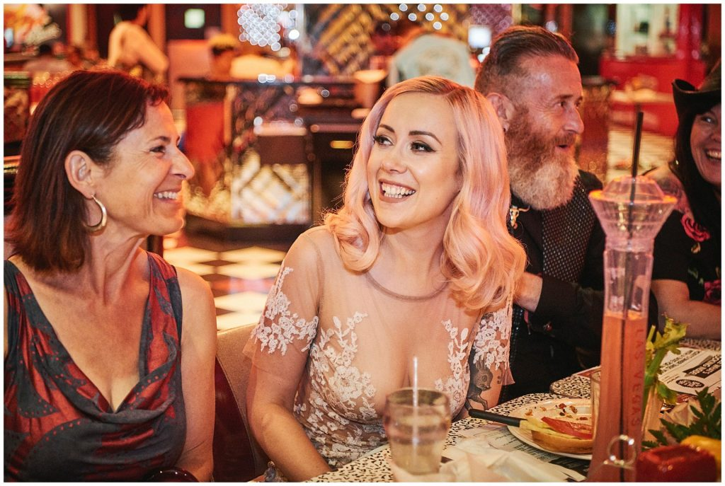 Happy bride sat with family in an American 50s themed diner