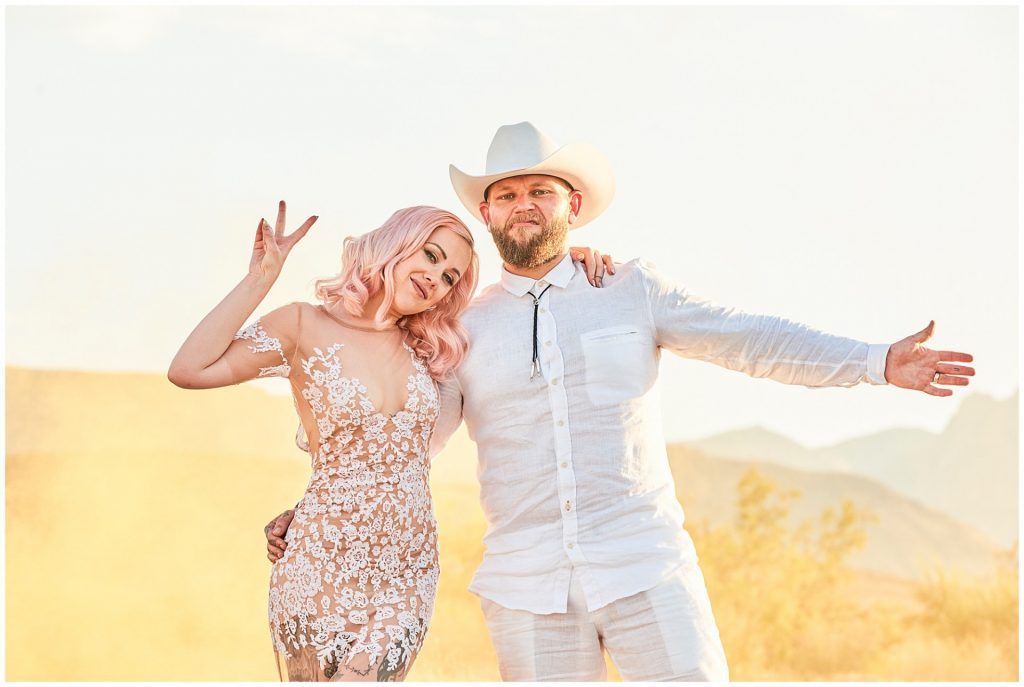 Alternative bride and groom stood in the desert during rock n roll wedding.