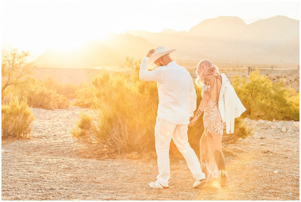 Alternative wedding couple walking through yellow smoke in Las Vegas desert