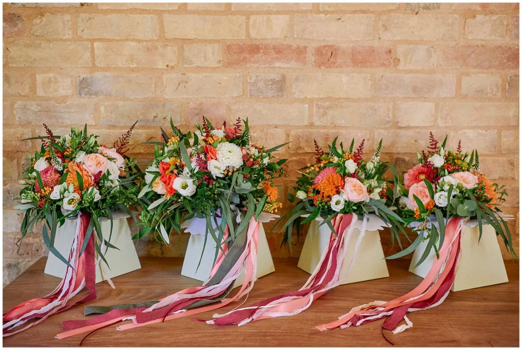 colourful wedding flower bouquets lined up against brick wall