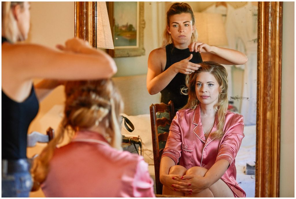 bride in pink pyjamas looking in mirror whilst having her hair styled