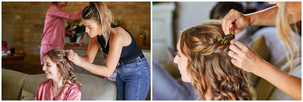 bridesmaid laughing whilst having her hair styled in a rustic barn