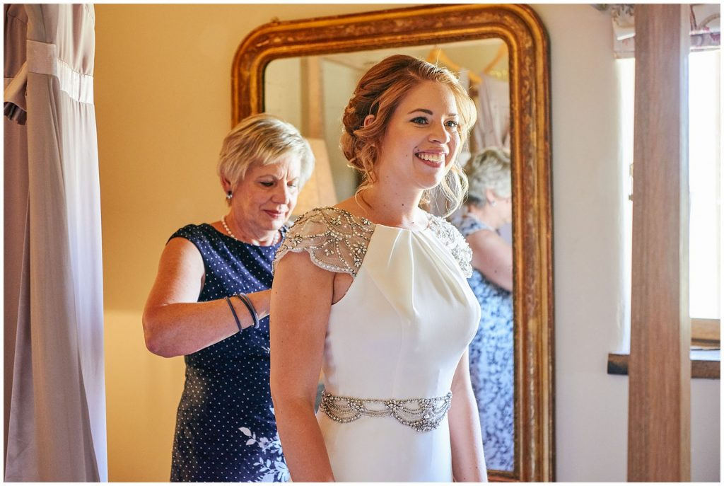 bride smiling whilst her mum does up her wedding dress