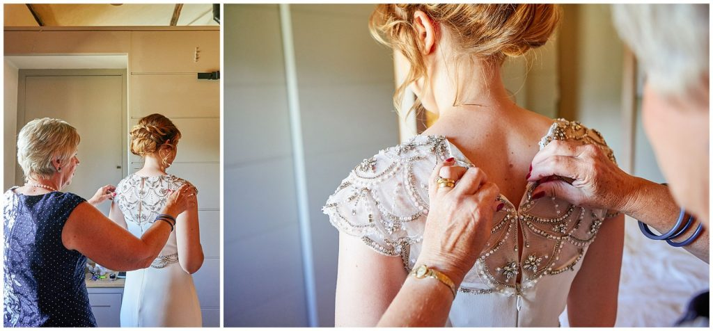 bride having her lace dress buttoned up by her mum