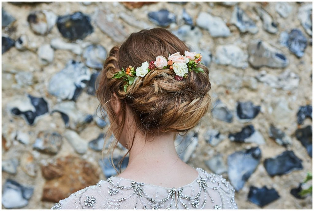 brides up do hair style with flowers and curls against a stone wall