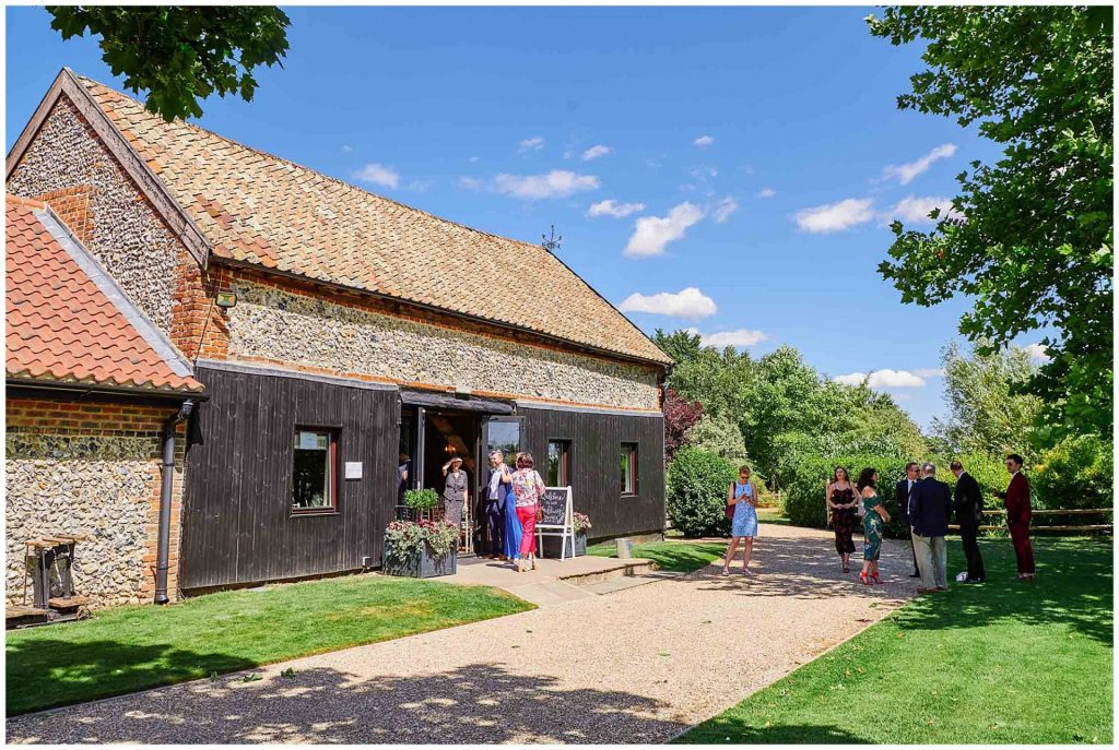 Wedding guests arriving on a sunny day with blue sky at the rustic looking Granary Estates barn in Cambridge.