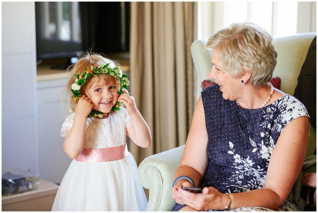Flower girl wearing a white dress and holding flower crown up to her face and smiling whilst grandma laughs