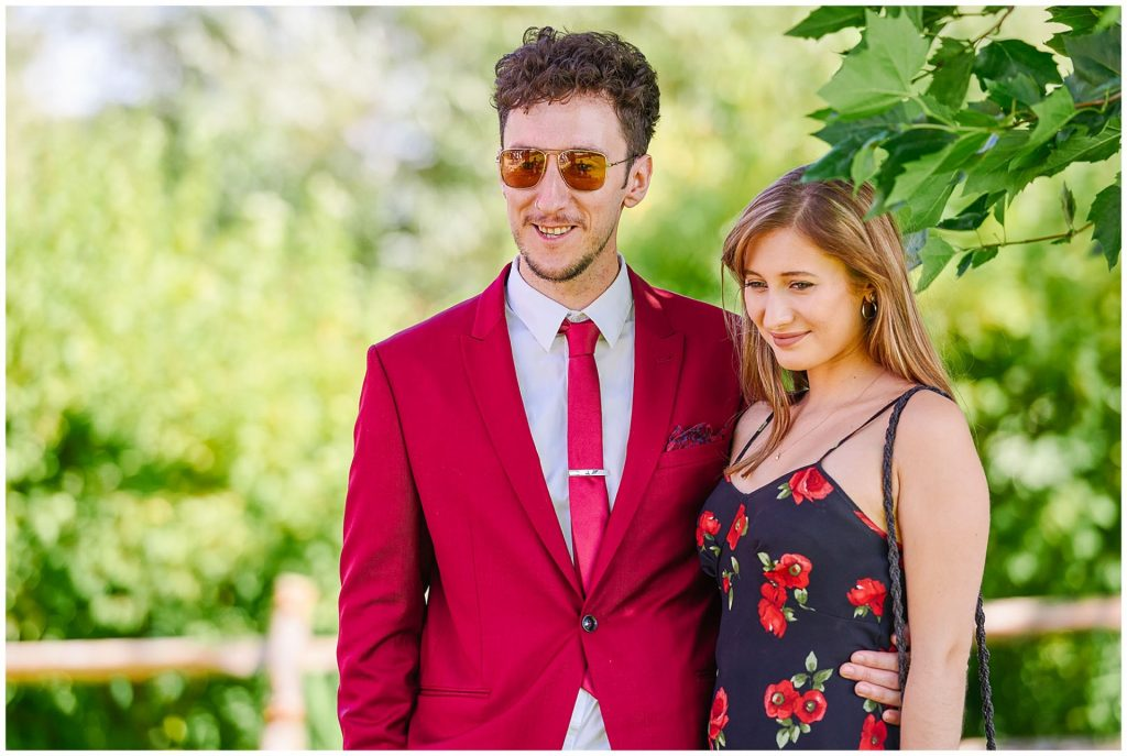 Male wedding guest wearing a red suit with his girlfriend both smiling together on a sunny day against a green leafy background.