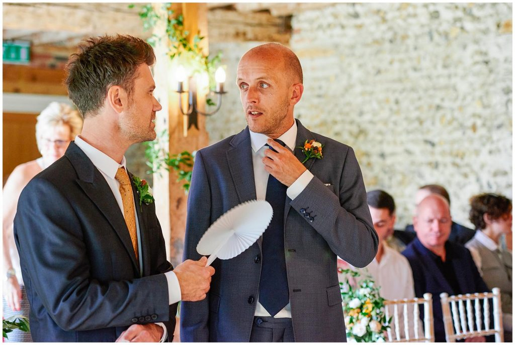 Groom adjusting his tie whilst stood with his best man during his wedding cermony at The Granary Estates stone barn in Cambridge.