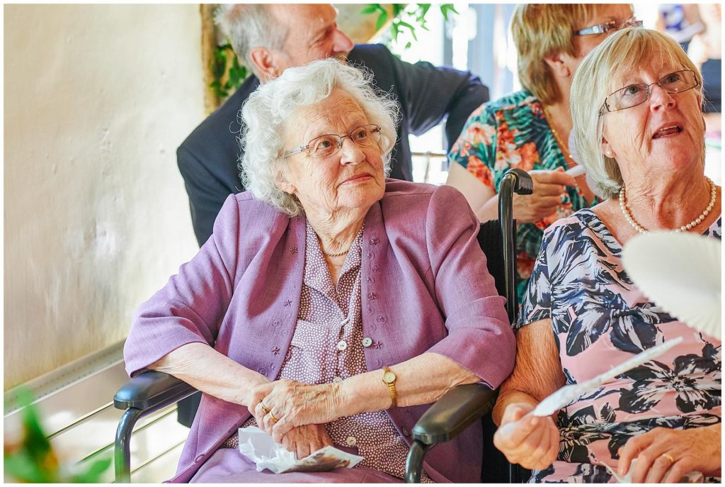 Grandma sat wearing a purple outfit during wedding ceremony at The Granary Estates stone barn in Cambridge.