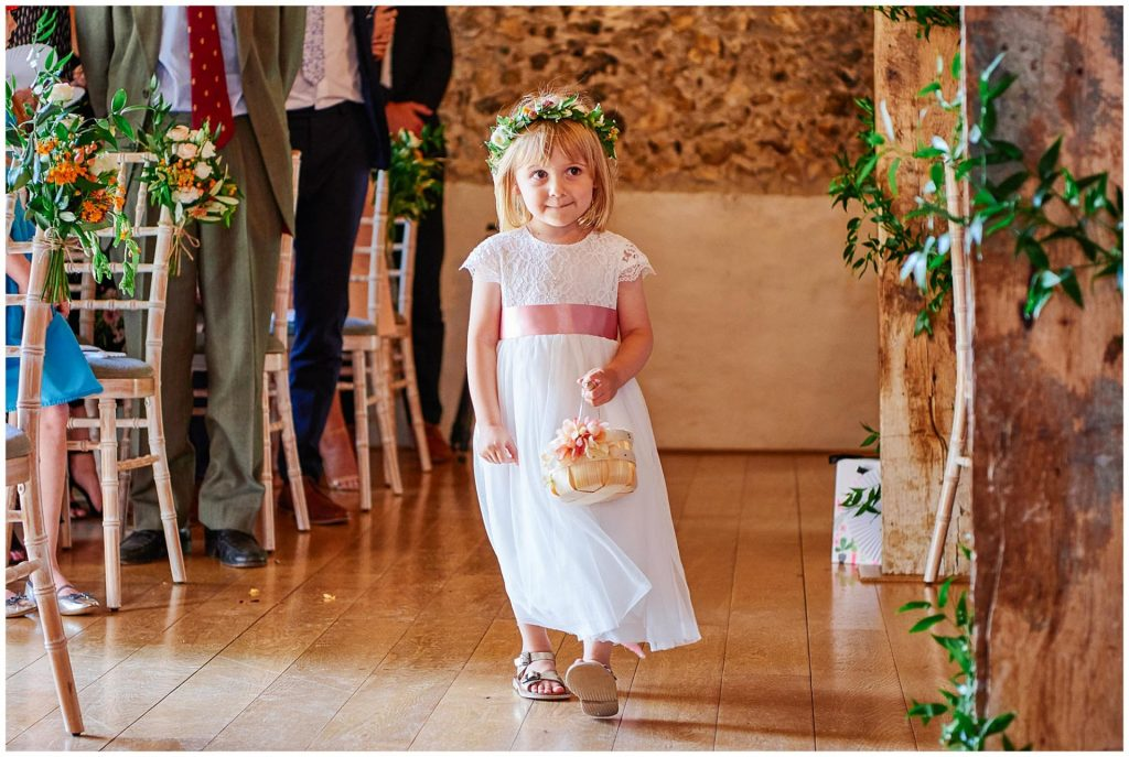 Flower girl walking down the aisle at The Granary Estates stone barn in Cambridge.