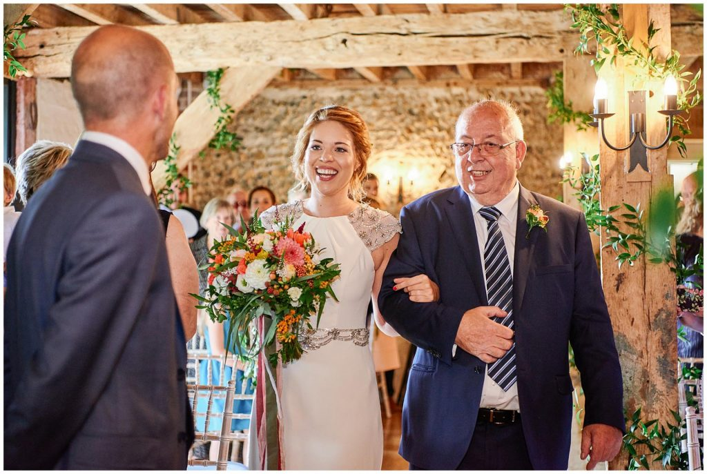 Bride and her dad walking down the aisle to meet groom at The Granary Estates stone barn in Cambridge.