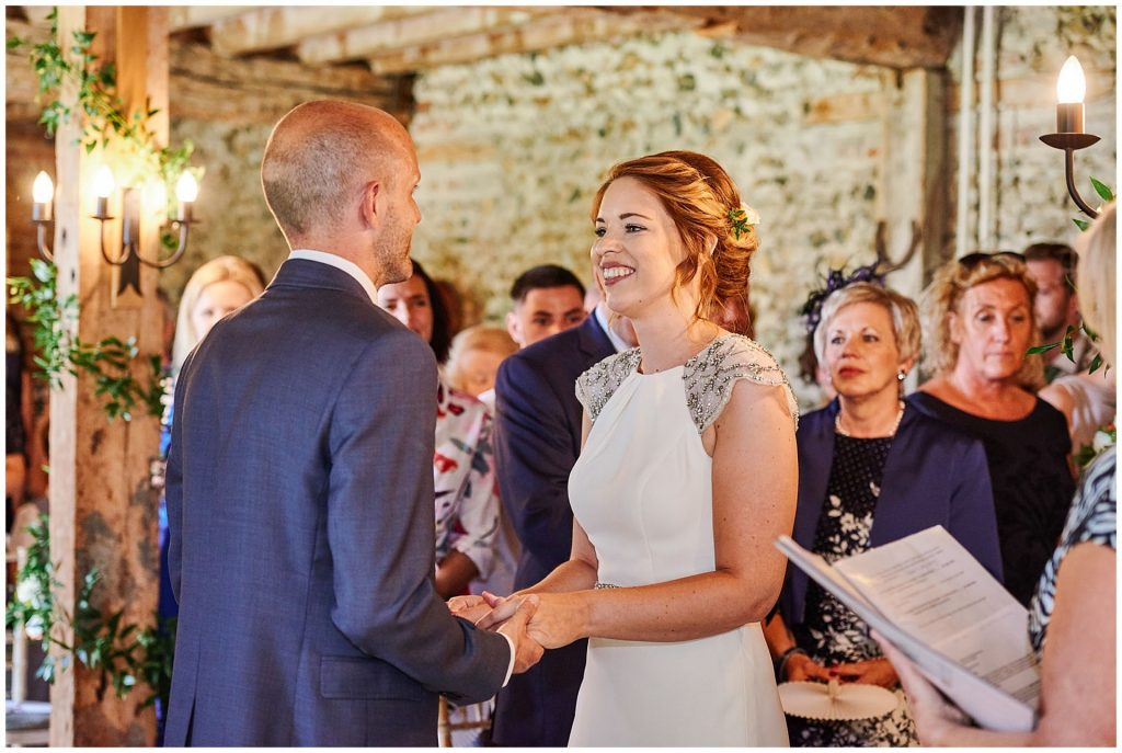 Bride and groom smiling at each other and holding hands during wedding ceremony at The Granary Estates stone barn in Cambridge.