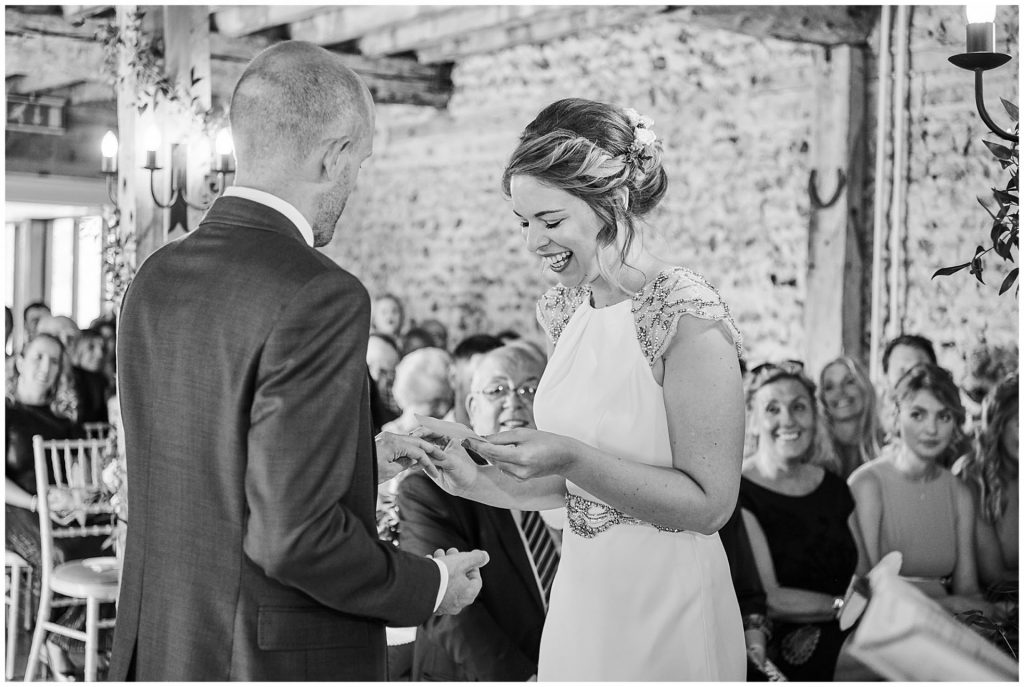 Bride and groom exchanging rings and laughing during wedding ceremony at The Granary Estates stone barn in Cambridge.