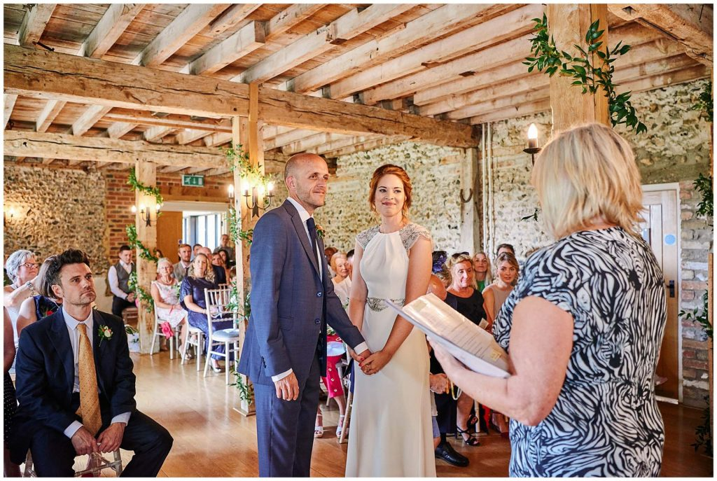 Bride and groom holding hands and smiling during wedding ceremony at The Granary Estates stone barn in Cambridge.