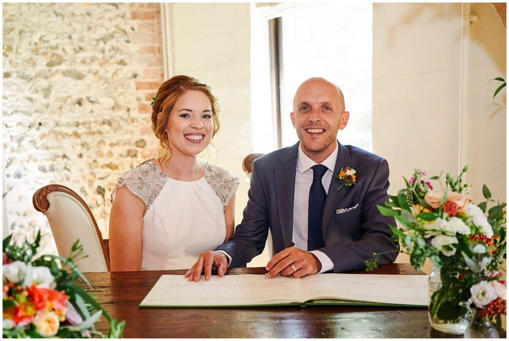 Bride and groom signing the register during wedding ceremony at The Granary Estates stone barn in Cambridge.