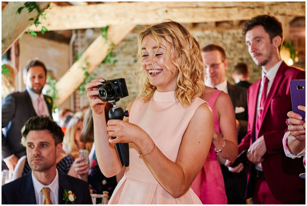 Happy wedding guest taking a photo  during the ceremony at The Granary Estates stone barn in Cambridge.