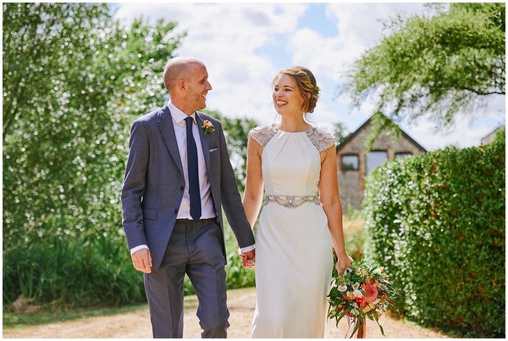 Bride and groom laughing whilst walking outside together with The Granary Estates barn in the background.