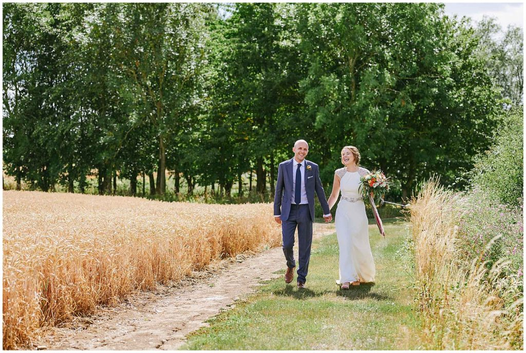 Bride and groom laughing whilst walking outside through a field at Granary Estates barn in Cambridge