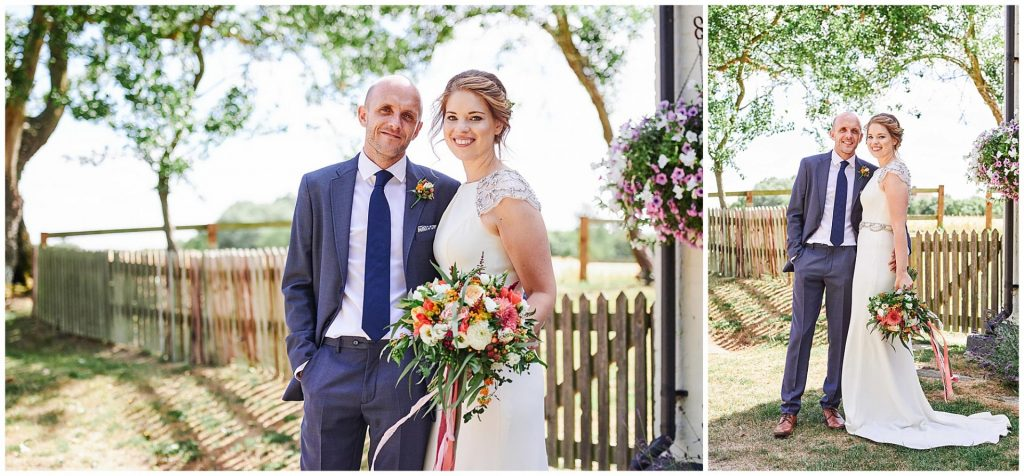 Happy bride and groom stood outside on a sunny day in front of a wooden fence at The Granary Estates in Cambridge