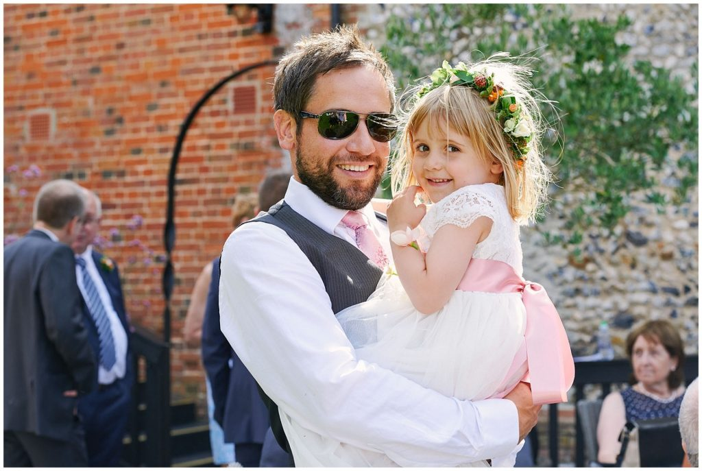 Wedding guest holding the flower girl whilst stood outside on a sunny day at The Granary Estates in Cambridge