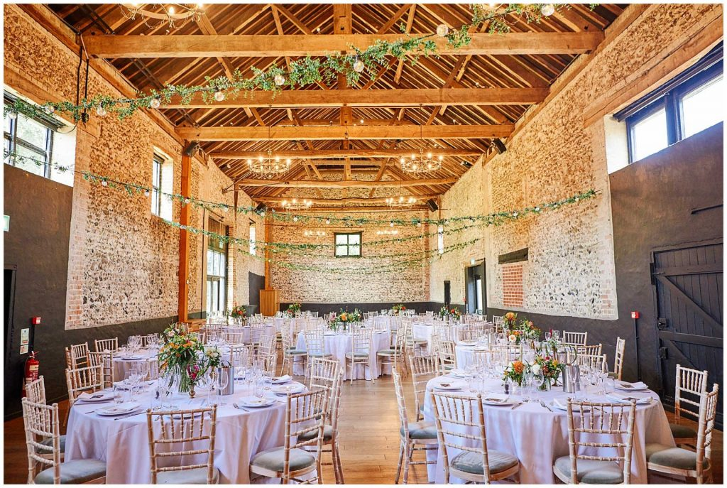 Empty wedding breakfast room with round tables, brick walls and rustic wooden beams at the Granary Estates in Cambridge.