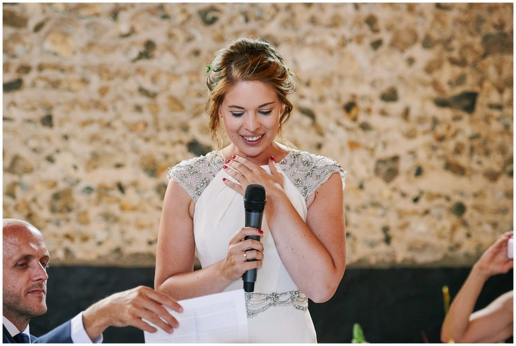 Bride giving an emotional wedding speech in a brick room at the Granary Estates in Cambridge.