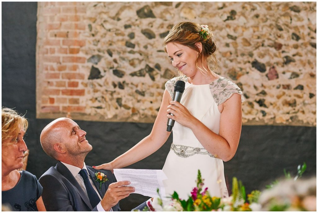 Bride giving an emotional wedding speech to her groom in a brick room at the Granary Estates in Cambridge.