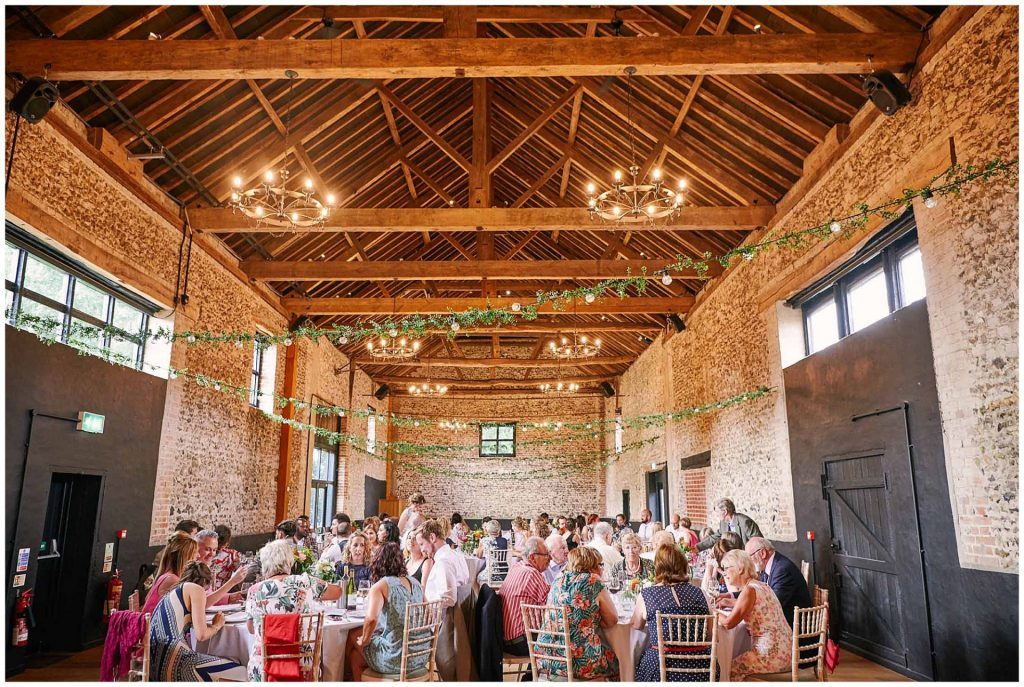Wedding guests sat down enjoying dinner in a rustic wooden and brick barn room at the Granary Estates  in Cambridge.