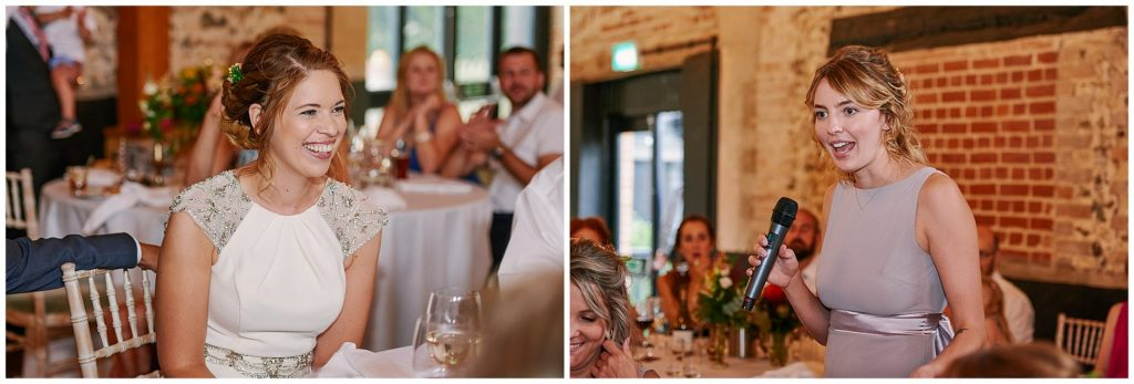 Bridesmaids giving a speech and bride laughing in a brick barn room at the Granary Estates in Cambridge.