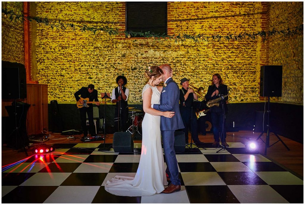 Bride and Groom dancing together on a black and white checkered dance floor at the Granary Estates in Cambridge.