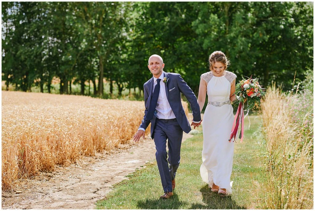 Bride and groom laughing whilst walking outside a sunny day at The Granary Estates barn in Cambridge