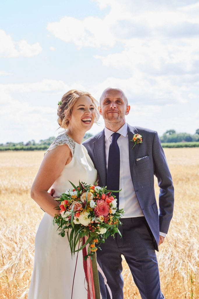 Bride and groom laughing together whilst stood in a field on a sunny day at The Granary Estates in Cambridge