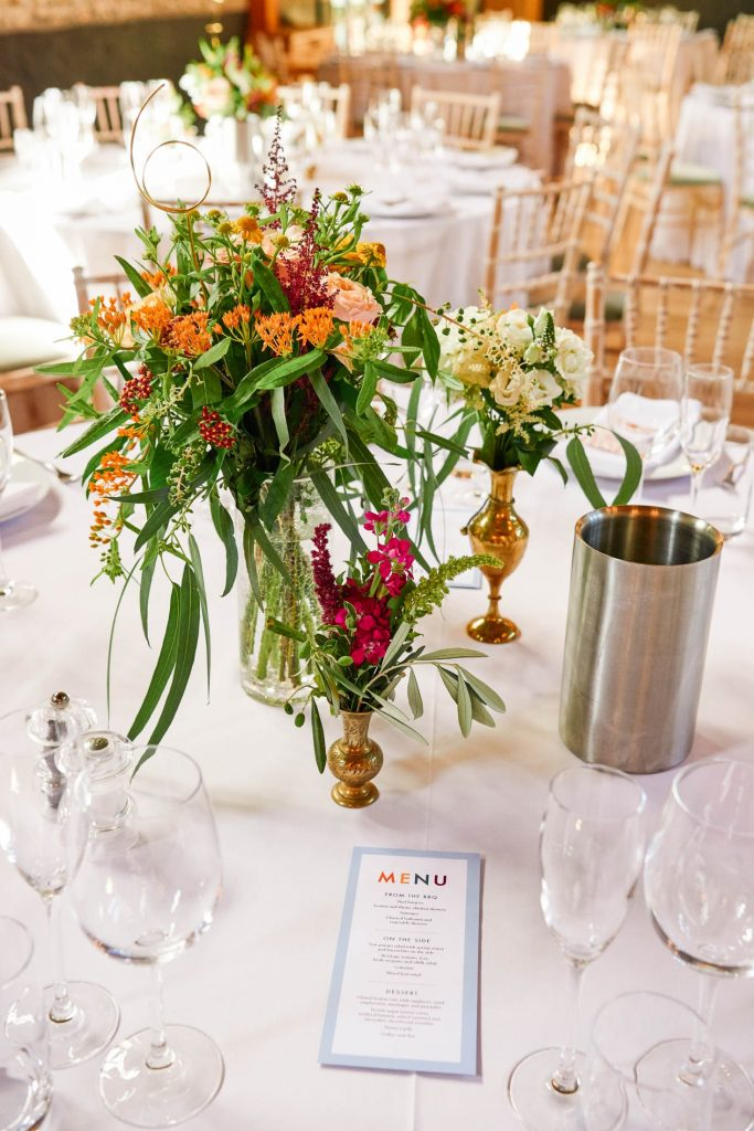 Flower bouquet on wedding breakfast table with menu and drinks glasses