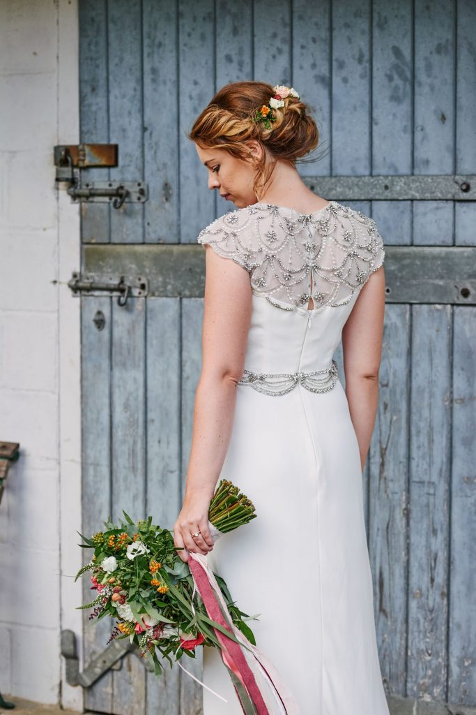 back of brides white wedding dress with flowers in her hand against a blue barn door in Cambridge