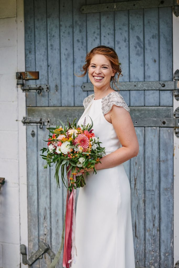 smiling bride holding colourful flowers and wearing a white wedding dress stood in front of a blue barn door in Cambridge