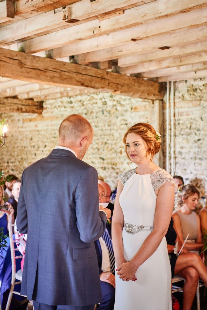 Bride and groom smiling at each other during wedding ceremony at The Granary Estates stone barn in Cambridge.