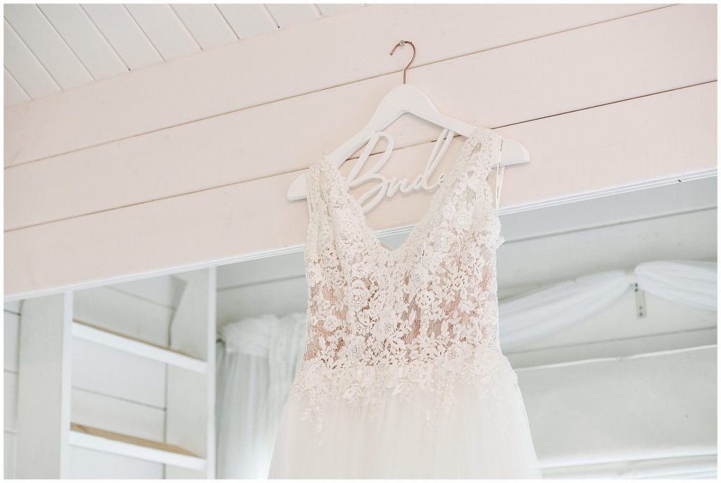 lace wedding dress hung up in white wooden bridal roo