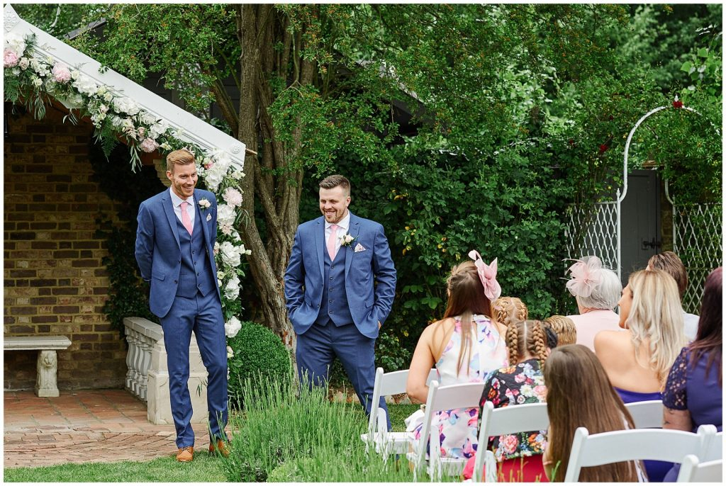 groom and usher smiling during outdoor ceremony in the walled garden at Marleybrook House
