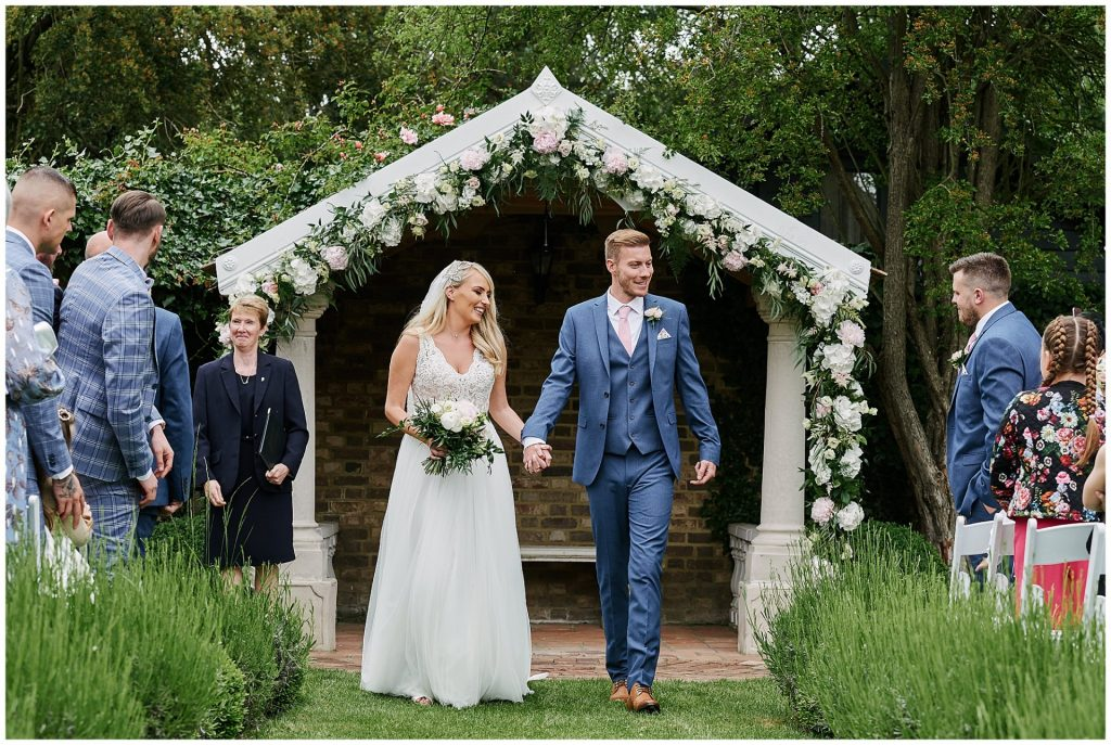 bride and groom walking down aisle during outdoor wedding ceremony at Marleybrook House