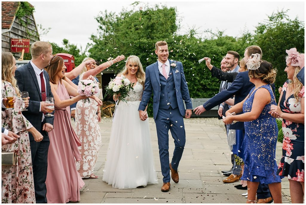 happy bride and groom walk through guests throwing confetti at Marleybrook House
