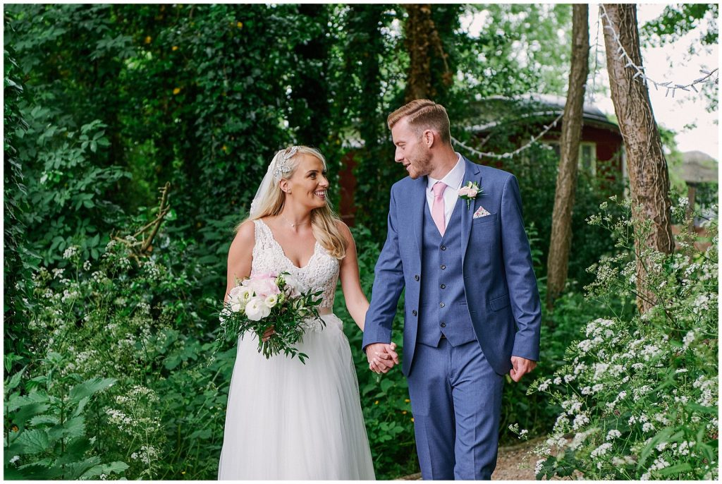 bride and groom walking through woodland together and smiling