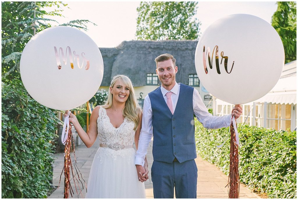 Bride and groom holding Mr and Mrs wedding balloons at Marleybrook House
