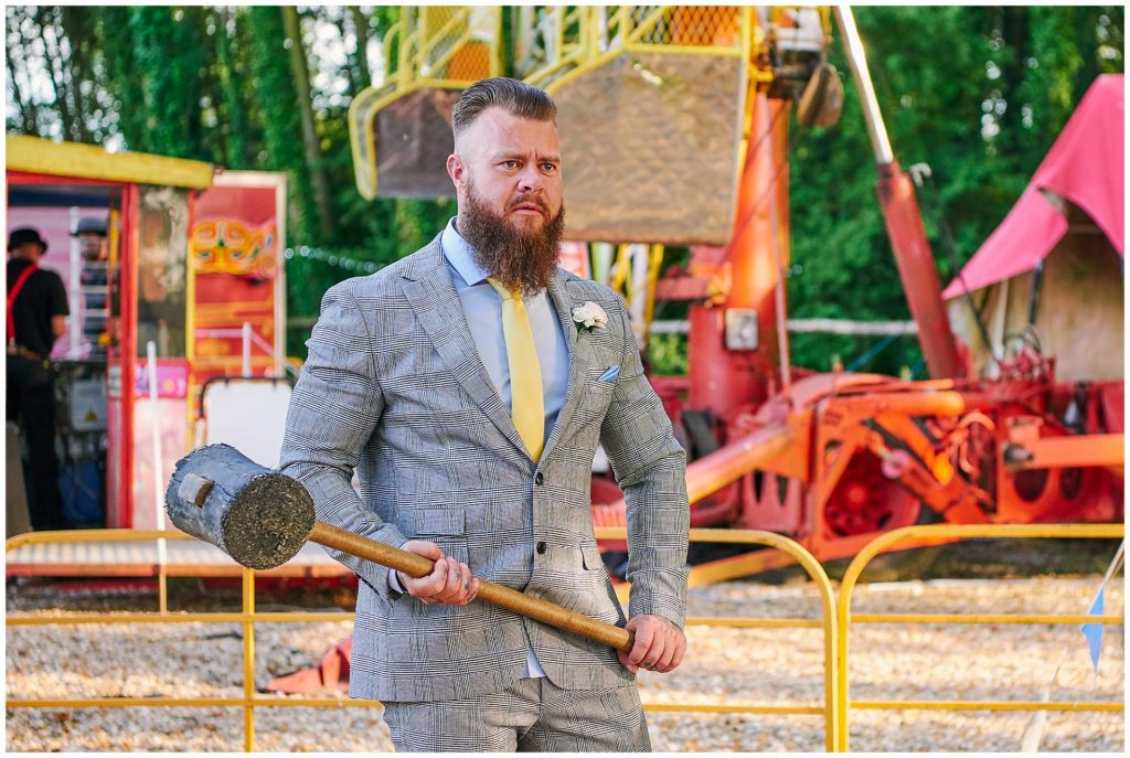 wedding guest holding a hammer at a unique funfair wedding venue